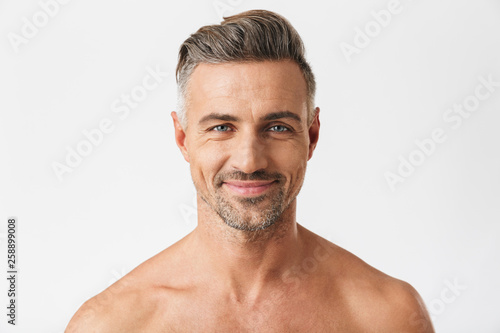 Fototapeta Closeup portrait of european half naked man 30s having bristle smiling at camera obraz