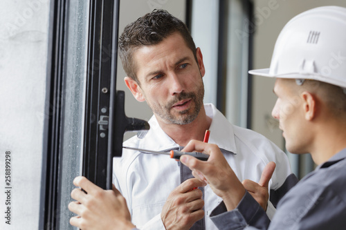 Pinturas sobre lienzo  smiling man is fixing a window handle