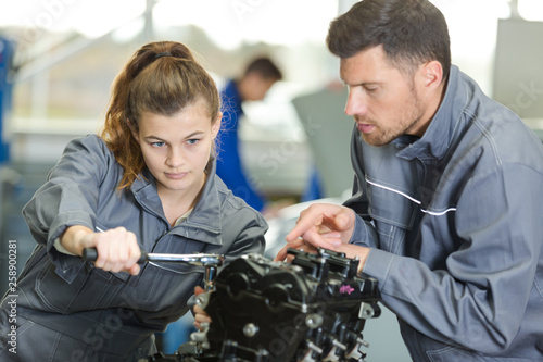 Fotografía auto mechanic guiding a female trainee in garage