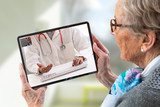 Fototapeta Dmuchawce - Senior woman consults a e-health doctor with tablet computer sitting in soft chair. In touchscreen, male doctor: With telehealth application patient can reach relevant specialist remotely.