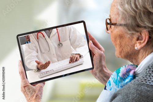 Senior woman consults a e-health doctor with tablet computer sitting in soft chair. In touchscreen, male doctor: With telehealth application patient can reach relevant specialist remotely.