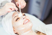 Cosmetology. The Cosmetologist Applies A Cleansing Face Mask. Smiling Girl On The Procedure For Facial Rejuvenation. Spa Facial Procedure.