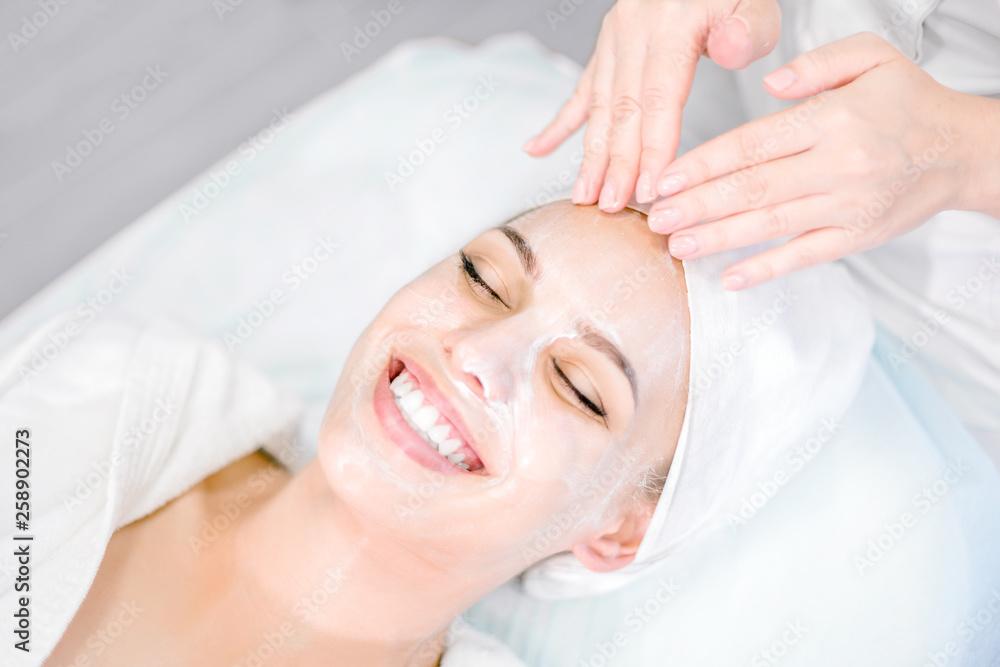 Fototapeta Beautician makes facial massage with mask. Beautiful smiling girl on spa procedure. Facial care.