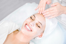 Beautician Makes Facial Massage With Mask. Beautiful Smiling Girl On Spa Procedure. Facial Care.