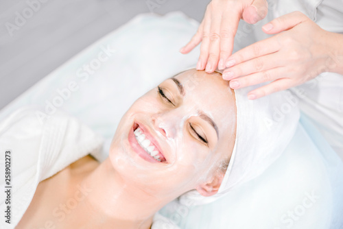 Fototapeta Beautician makes facial massage with mask. Beautiful smiling girl on spa procedure. Facial care. obraz