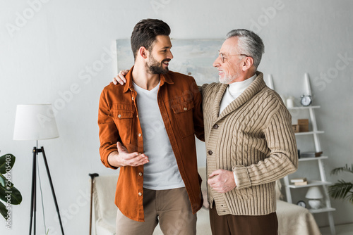 Fotografia handsome man gesturing and looking at cheerful senior father