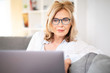canvas print picture - Frau mit Brille zuhause auf der Couch mit laptop