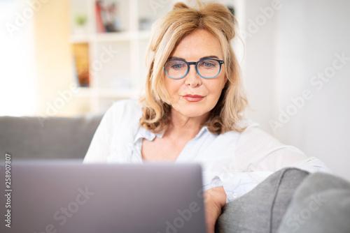 Fotografía  Frau mit Brille zuhause auf der Couch mit laptop