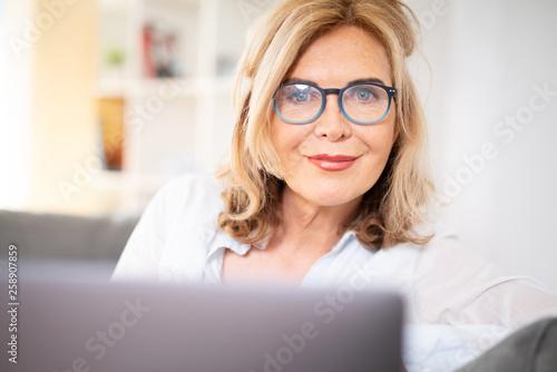 Fotografia  Frau mit Brille zuhause auf der Couch mit laptop