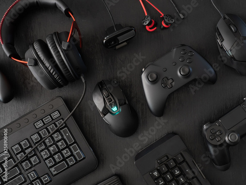 Photo  gamer work space concept, top view a gaming gear, mouse, keyboard, joystick, headset, mobile joystick, in ear headphone and mouse pad on black table background