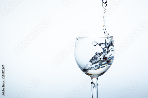 Photo sur Aluminium Bar Water splashing in the luxury wine glass close up. Concept of good healthy and refreshment. Copy space on left side on the image.