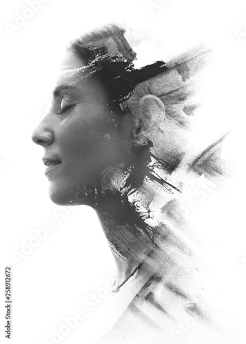 Fototapeta Paintography. Double exposure portrait of a young woman's profile combined with handmade painting with a texture of brushstrokes disappearing into her face. Black and white obraz na płótnie