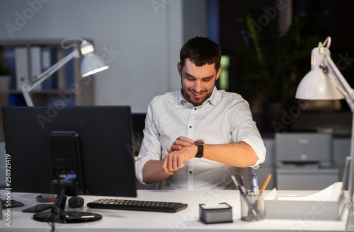 business, technology and time management concept - happy smiling businessman with smart watch at nigh office