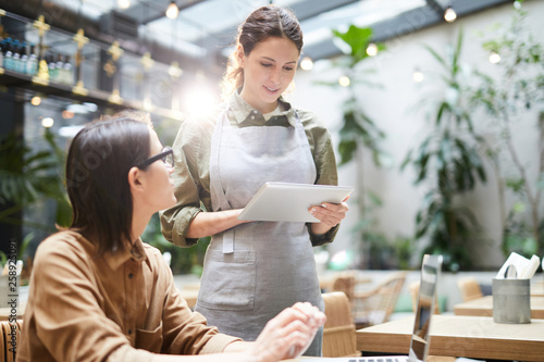 Content attractive waitress in apron standing at table and adding information in Fototapet