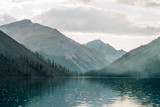 Amazing huge cloud above giant mountains. Raindrops on mountain lake. Beautiful rain drops. Wonderful droplets on lake water. Low clouds. Cloudy sky. Wonderful atmospheric ghostly highland landscape. - 258925609