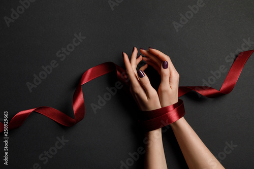cropped view of woman tied with silk red ribbon on black background Tableau sur Toile
