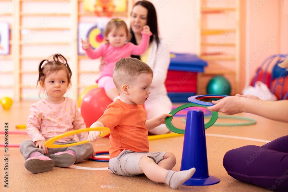 Fototapety, obrazy: Nursery babies group doing sport in gym
