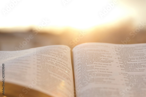 Valokuva  Open Bible with bright sunset in the background