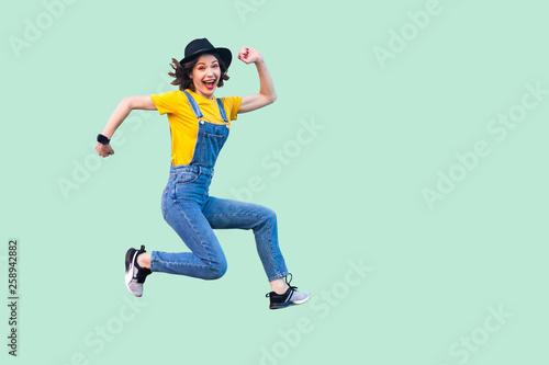 Photo  Portrait of happy carefree pretty young hipster girl in blue denim overalls, yellow shirt and black hat jumping, looking at camera and enjoying