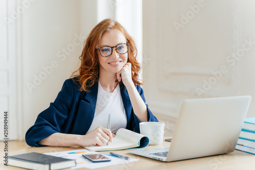 Successful economist in eyewear, checks information on laptop computer, reads information on financial website, writes in notepad and drink hot coffee, sits at workplace Wallpaper Mural