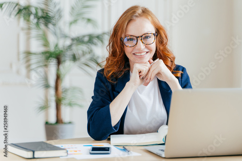 Pleased cheerful red haird female economist develops financial startup project, poses in office interior, works in business sphere, dressed in formal clothes, has happy expression, owns company