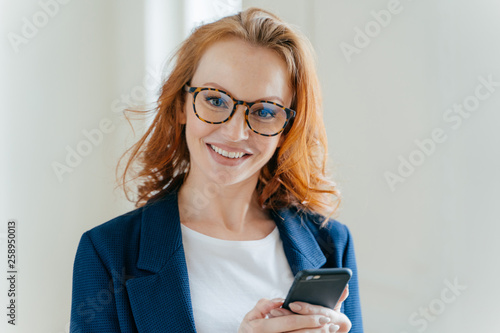 Close up shot of pretty redhead female directror has charming smile, dressed in elegant clothes, holds mobile phone, checks text message, surfs social networks, connected to wireless internet Fototapete