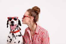 Portrait Of Happy Young Woman Kissing Her Dalmatian Dog. Pet And Girl In Red Sunglasses. Copy Space, Friendship Concept