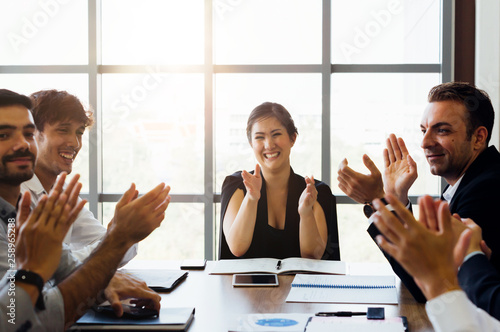 businesspersons clapping hands and applauding in business meeting conference. While female business executive sitting in front - woman power in corporate work