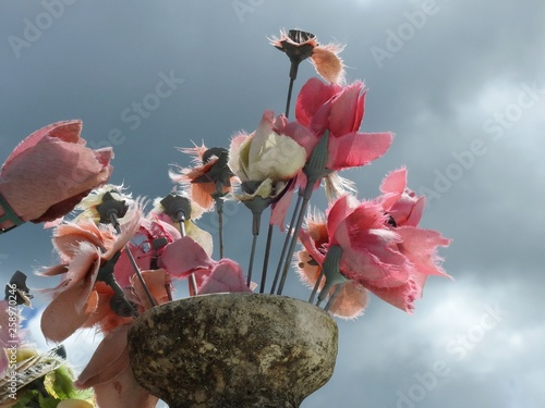 Fotografija Scene in a graveyard: an old stone vase with artificial pink flowers