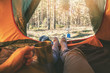 outdoor tourism - man laying in tent with cup of tea