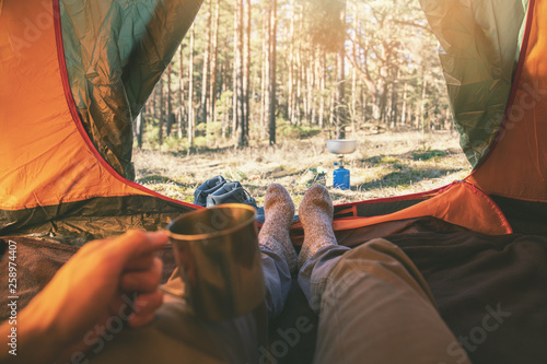 Obraz outdoor tourism - man laying in tent with cup of tea - fototapety do salonu