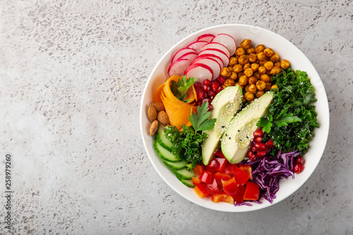 Photo  salad with avocado, roasted chickpeas, kale, cucumber, carrot, red cabbage, bel