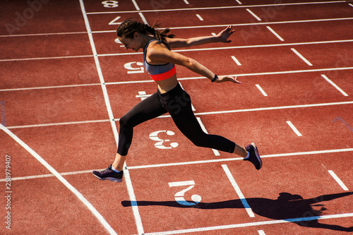 Fototapeta Side view of female teen athlete in sports bra and tights successfully finishing race on track at stadium  obraz