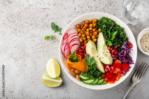 lunch bowl salad with avocado, roasted chickpeas, kale, cucumber, carrot, red cabbage, bell pepper and redish