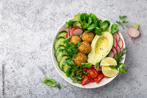 healthy vegan lunch bowl salad with avocado, falafel,cucumber, tomato and redish Canvas Print