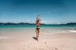 Girl at the sea. Attractive brunette in black bikini on the beach, rear view