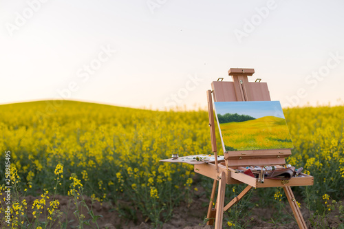 Slika na platnu easel with paints and canvas painting in the field
