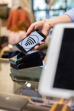 Customer Paying Contactless With Smartphone In A Fashion Store