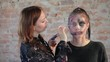 Close-up woman professional makeup artist makes wax plastic makeup in form of bloody wound for art cinema and paints face of cute girl and creates image for shooting scene on background brick wall