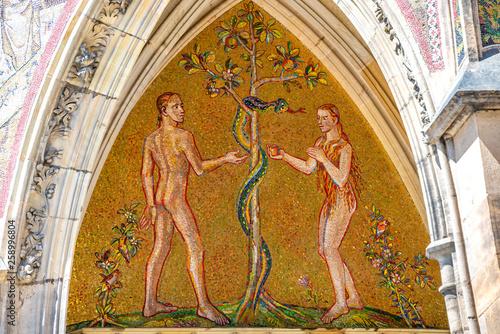 Vászonkép Bible scene of Genesis with Adam and Eva at major entrance portal of Saint Vitus