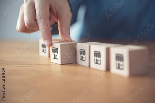 Fototapeta  Closeup Woman hand choose wood blog with franchise icon