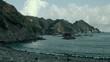 Static shot across Izu, Japan, Rocky coastal beach. Looking across Pacific ocean towards high stone cliff face along the horizon.
