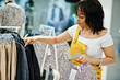 canvas print picture - African american woman choosing clothes at store. Shopping day.