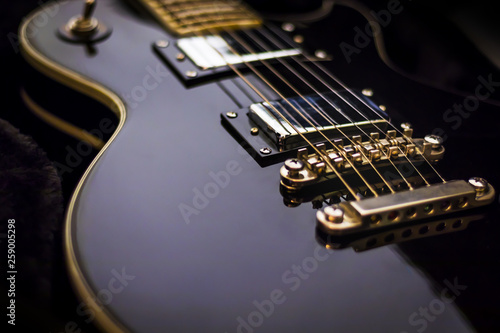 Photo  Black electric guitar closeup on a dark background