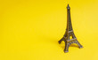 Leinwanddruck Bild - photo of Eiffel Tower shaped souvenir on the wonderful yellow studio background