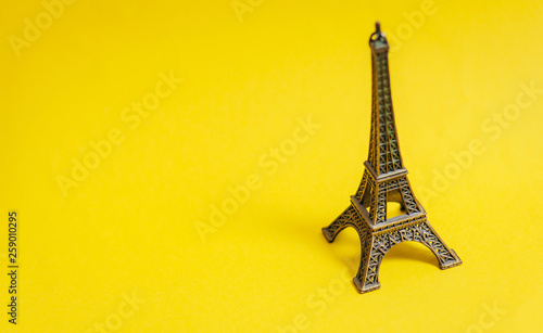 Foto auf Leinwand Eiffelturm photo of Eiffel Tower shaped souvenir on the wonderful yellow studio background