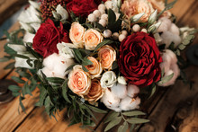 Bridal Bouquet With Red And Orange Flowers. Roses And Peonies, On The Background Of A Wooden Bench.