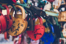 Close Up Of A Love Lock On A Railing On A Locks Bridge With Other Locks Blurred To Create A Bokeh Background.