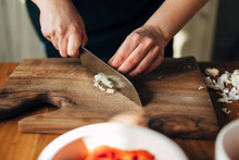 Chef Chopping Garlic With Knife On A Wooden Board