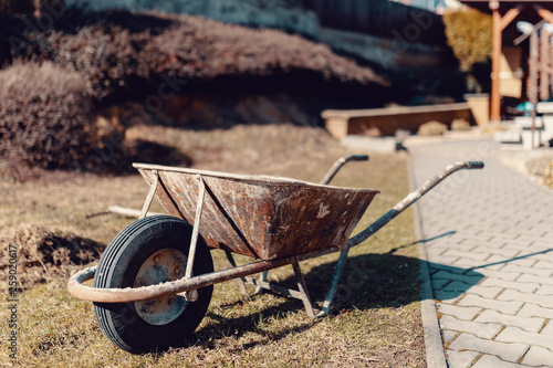 Fotografía  empty old rusty garden wheelbarrow in spring time